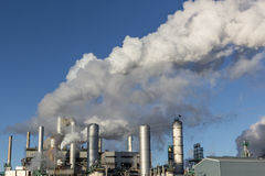 Oil refinery. Factory towers blowing steam Stock Image