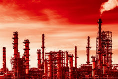 Oil refinery and global warming. Oil refinery with smoke from the pipe. Black and white photography with red tint to show danger and global warming royalty free stock photos