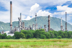 Oil refinery with green field Royalty Free Stock Image