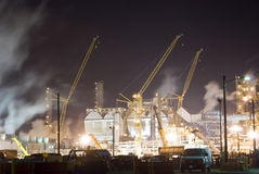Oil refinery industrial crane. An oil refinery in the United States with a series of foggy and smoky stacks. Cranes and steam Stock Photos