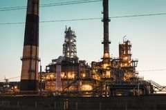 Oil refinery industrial plant or factory at sunset, storage distillery tanks and steel pipeline, modern petrochemical technologies. Toned royalty free stock photo