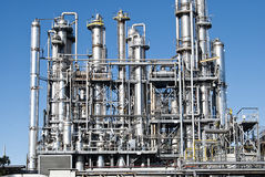 Oil refinery industry distillation pipelines. Industrial shot of shining distillation pipelines of oil refinery industry on blue sky Stock Photo