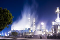 Oil refinery insdustrial. An oil refinery in the United States with a series of foggy and smoky stacks. Glowing mist Royalty Free Stock Photography