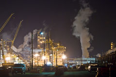 Oil refinery Mist and cranes. An oil refinery in the United States with a series of foggy and smoky stacks. Cranes and lights in the complex Royalty Free Stock Photo