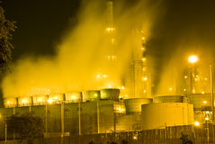 Oil refinery Misty smog. An oil refinery in the United States with a series of foggy and smoky stacks. Yellow glowing image of misty smoke stacks Royalty Free Stock Photos