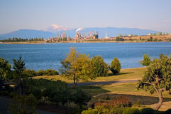Oil Refinery and Mount Baker on Puget Sound. An oil refinery and tanks on the Puget Sound at Anacortes Island, Washington, with Mount Baker in the distance and a Royalty Free Stock Images