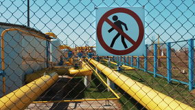 Oil refinery. Natural gas treatment plant. Storage of oil products and gas. Warning sign of danger. Unauthorized entry. Is prohibited. Pipeline with shut-off stock video footage