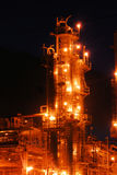 Oil Refinery at Night. A column in an oil refinery in operation with columns, tanks, and piping against a night sky Stock Images