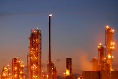 Oil Refinery at Night. A refinery in operation with columns, tanks, and piping against a blue evening sky Royalty Free Stock Photos