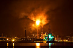 Oil refinery at night with a huge smoke column Royalty Free Stock Photo