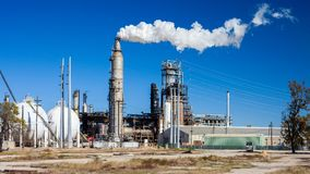 Oil refinery plant with chimney blowing smoke Royalty Free Stock Image