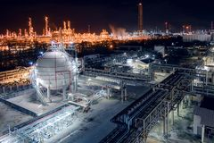 Oil refinery plant. Gas storage sphere tanks and pipeline in oil and gas refinery industrial plant with glitter lighting industry estate at night royalty free stock images