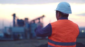 Oil refinery plant at sunrise with sky background,silhouette and Power plant,blur,bokeh. Engineer in a helmet on the. Working engineer in a helmet on the stock video