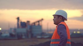 Oil refinery plant at sunrise with sky background,silhouette and Power plant,blur,bokeh. Engineer in a helmet on the. Working engineer in a helmet on the stock video footage