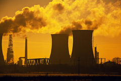 Oil refinery pollution. Evacuation towers with smoke, dramatic sky Royalty Free Stock Image