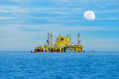 Oil  refinery into the sea with moon on sky Royalty Free Stock Image