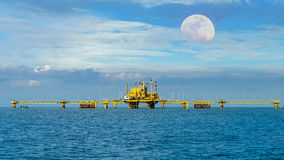 Oil  refinery into the sea with moon on sky Stock Photography