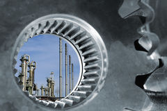 Oil refinery seen through large gears axle Royalty Free Stock Photo