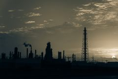 Oil refinery silhouette at sunrise. Silhouette oil refinery at sunrise. Oil factory, petrochemical plant tower, gas flare, smoke stacks and machinery in Corpus Stock Photo