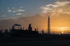 Oil refinery silhouette at sunrise. Silhouette oil refinery at sunrise. Oil factory, petrochemical plant tower, gas flare, smoke stacks and machinery in Corpus Stock Photos