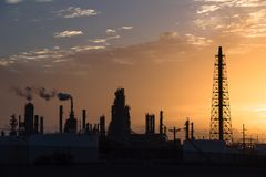 Oil refinery silhouette at sunrise. Silhouette oil refinery at sunrise. Oil factory, petrochemical plant tower, gas flare, smoke stacks and machinery in Corpus Stock Image