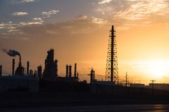 Oil refinery silhouette at sunrise. Silhouette oil refinery at sunrise. Oil factory, petrochemical plant tower, gas flare, smoke stacks and machinery in Corpus Royalty Free Stock Images
