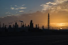 Oil refinery silhouette at sunrise. Silhouette oil refinery at sunrise. Oil factory, petrochemical plant tower, gas flare, smoke stacks and machinery in Corpus Stock Images
