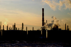 Oil refinery silhouetted. Smokestacks and industrial vents silhouetted at an oil refinery stock images
