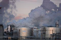 Oil Refinery Spewing Gas Emissions. Oil refinery with storage tanks spewing gas emissions into the air stock images