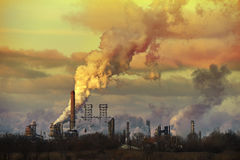 Oil refinery spewing smoke at sunset Stock Photos