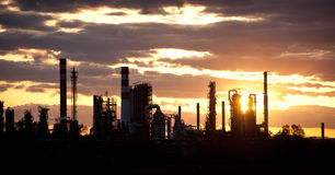 Oil refinery at sunset. Oil refinery with sun setting behind it Royalty Free Stock Images