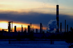 Oil refinery at sunset. Scenic view of chimneys of oil refinery silhouetted with sunset and cloudscape background, Edmonton, Alberta, Canada stock photos