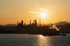 Oil refinery before a sunset. Moorings and the territory of oil refinery, with the serving vessels before a sunset Royalty Free Stock Photography