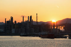 Oil refinery at sunset. Moorings and the territory of oil refinery, with the serving vessels at sunset Royalty Free Stock Photography