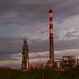 Oil refinery tower and chimney at dusk Stock Photo