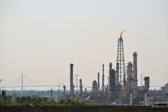 Oil refinery tower with exhausted flame Stock Photos