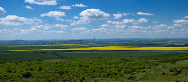 The oil refinery among the yellow rapeseed fields on the backgro. Und of the Balkan Mountains, modern technologies of people and the nature in the springtime Stock Images