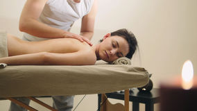 Oil relax massage - man`s hands on the nude back of the black hair girl. Close up stock photography