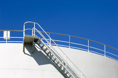 Oil reservoir. Detail with acess ladder against a blue sky Royalty Free Stock Photo
