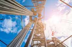 Oil rig on the background of blue, clouds and sun Royalty Free Stock Images