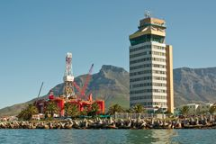 Oil- rig in bay of big city ne. Oil- rig in the bay into a big city  with tower buildings near ocean and mountains. cape town, south africa Stock Photo
