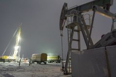 Oil rig and brightly lit industrial site at night. Blur photo effect. Extraction of oil. stock photo