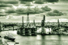 Oil Rig with cranes in Vittoriosa, Valletta. MALTA - 06 JAN 2016: Oil Rig with cranes in Vittoriosa, Valletta HDR black and white photography Stock Photography