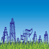 Oil rig and pump over blue background with grass. Royalty Free Stock Photography