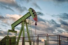 Oil rig pumping. On blue cloudy sky background stock photography
