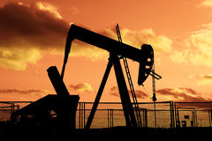 Oil rig pumping on cloudy sky Stock Photo