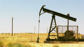 Oil rig pumping oil. A stationary shot of an oil rig pumping oil in a field near Bakersfield stock footage