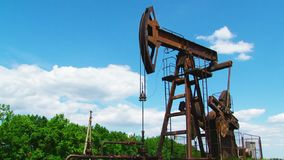 The oil rig pumps oil. Rusty oil rigs pump oil against the blue sky stock footage