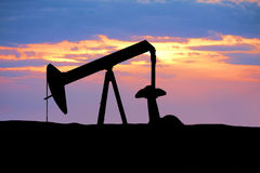 Oil Rig Silhouette. Oil rig sitting in the middle of the prairie stock image