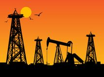 Oil rig silhouettes. And orange sky Royalty Free Stock Photo